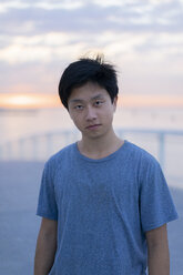 Young Chinese man at beach at sunrise, portrait - AFVF00712