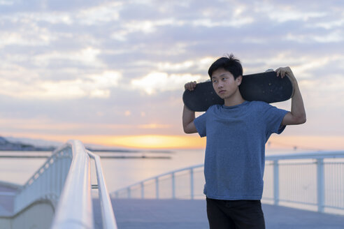 Young Chinese man with skateboard at the beach at sunrise - AFVF00715