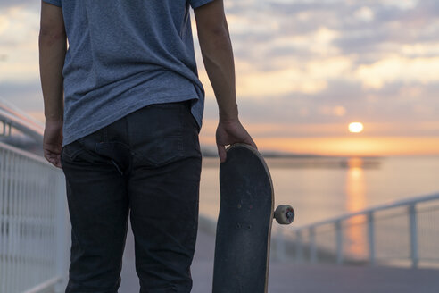 Young man with skateboard at the beach at sunrise, rear view - AFVF00718