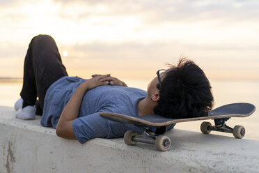 Young Chinese man with skateboard lying on wall at the beach - AFVF00724