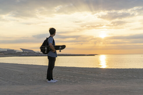 Young Chinese man with skateboard standing at the beach at sunrise - AFVF00727