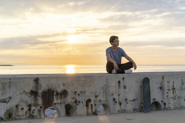 Young Chinese man sitting on wall at sunrise - AFVF00730