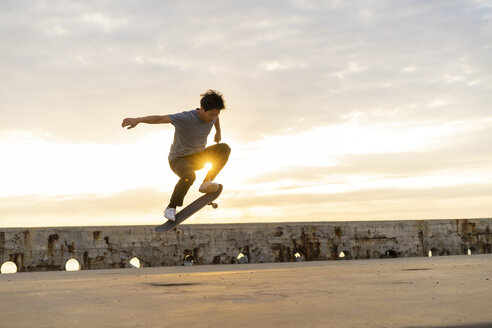 Young Chinese man skateboarding at sunsrise near the beach - AFVF00733