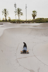 Young Chinese man resting on skateboard near the beach - AFVF00736