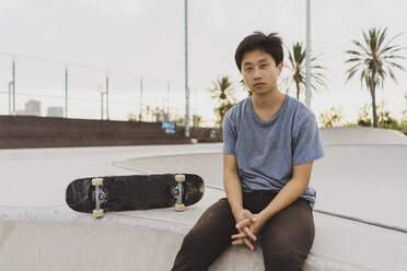 Young Chinese man sitting on wall of a skate park near the beach - AFVF00739