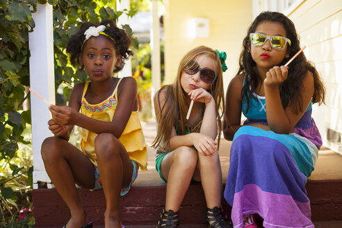 Three girls pulling faces on porch - ISF16683