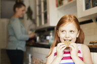 Girl eating biscuit in kitchen - ISF16722