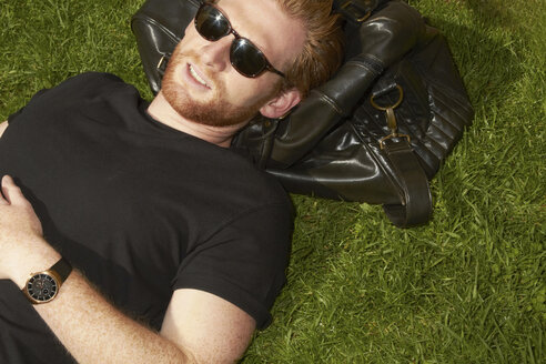Man laying on bag in grass - CUF39728