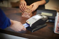 Cropped image of customer paying through credit card at checkout counter - MASF08037