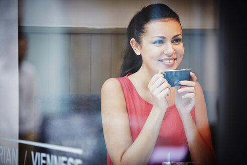 Young woman sitting in cafe with hot drink - CUF39888