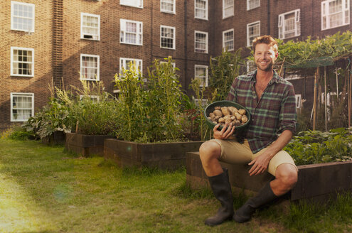 Mid adult man on council estate allotment with bowl of potatoes - CUF39951