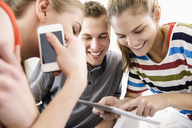 Three young adult friends looking at digital tablet - CUF40031