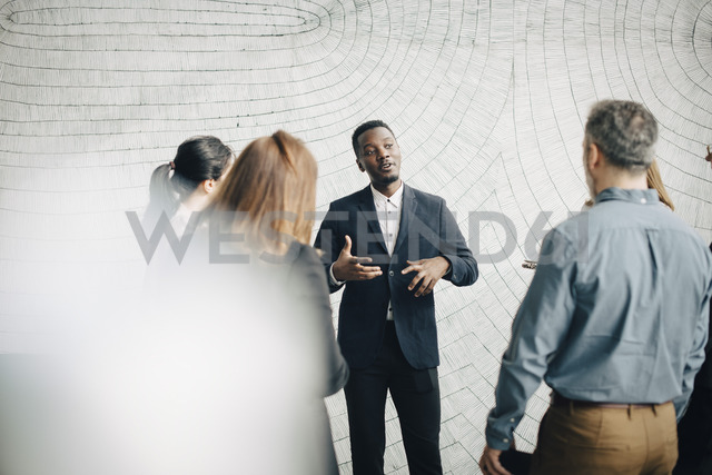 Young businessman discussing with colleagues in meeting at office - MASF08063