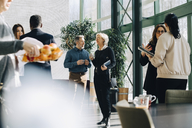 Businessmen and businesswomen planning while standing in office - MASF08084