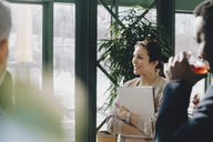 Businesswoman holding diary while talking to colleagues at office - MASF08087