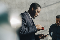 Young businessman using mobile phone while having tea at office - MASF08099