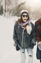Cheerful woman standing with friend on snow covered landscape - MASF08117