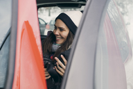 Smiling mid adult woman sitting in car seen through open door - MASF08132