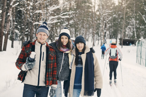 Portrait of smiling friends standing on snow covered field at park - MASF08150