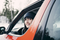 Portrait of smiling woman sitting in red car - MASF08162