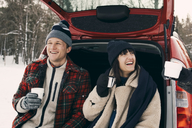 Happy woman having coffee while sitting with friends in car trunk during winter - MASF08165