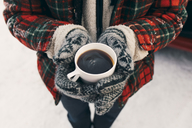Midsection of man holding coffee cup while standing on snow - MASF08168