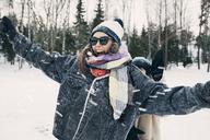 Happy woman enjoying with friend at snowy field - MASF08171