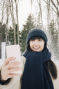 Smiling mid adult woman taking selfie through mobile phone during winter - MASF08180