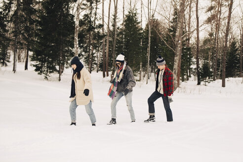 Full length of friends walking on snow by trees at park - MASF08186