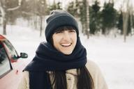 Portrait of smiling woman wearing scarf on snowy landscape - MASF08189