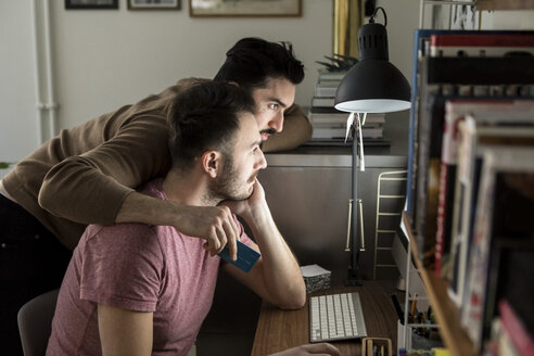 Gay couple shopping online through credit card on computer at illuminated desk in living room - MASF08192