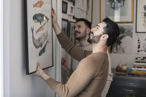Homosexual couple hanging painting on wall at home - MASF08198