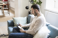 Young man doing online shopping on digital tablet through credit card while sitting on sofa at home - MASF08213