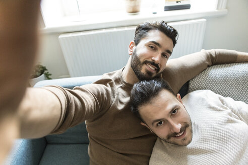 Smiling gay couple taking selfie while relaxing on sofa in living room at home - MASF08216