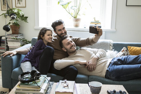 Fathers taking selfie with daughter through mobile phone on sofa at home - MASF08219