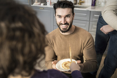 Smiling young father offering pancake to daughter in kitchen - MASF08231