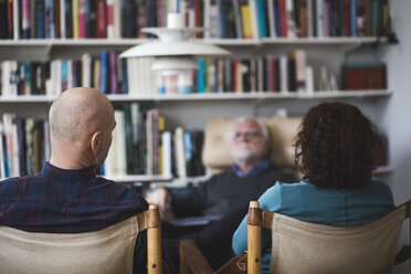 Mature couple discussing with therapist while sitting against bookshelf - MASF08249
