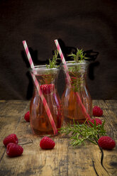 Two glass bottles of homemade raspberry lemonade flavoured with rosemary - LVF07234