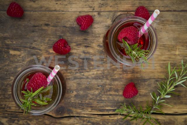 Two glass bottles of homemade raspberry lemonade flavoured with rosemary - LVF07240