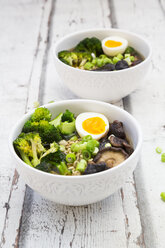 Two bowls of Ramen soup with egg, broccoli, noodles, shitake mushroom and spring onions - LVF07243