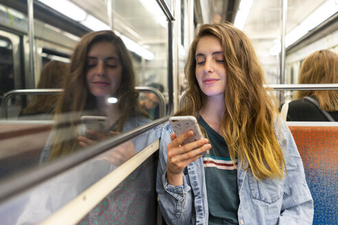 Smiling young woman in underground train looking at smartphone - AFVF00743