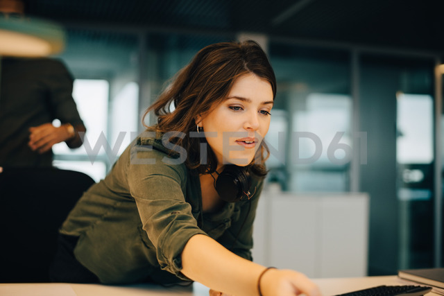 Confident businesswoman working at desk in creative office - MASF08253