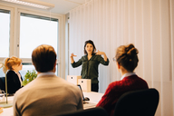 Confident businesswoman explaining strategy to colleagues sitting in board room at creative office - MASF08274