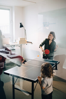 Boy looking at female professionals playing table tennis in creative office - MASF08286