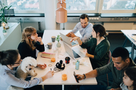 High angle view of business people sitting with boy and dog at desk in creative office - MASF08289