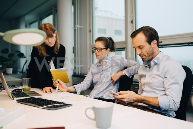 Businessman using smart phone while female colleagues discussing over document at desk in creative office - MASF08304