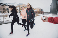 Cropped image of friend timing women running on snow covered street - MASF08316
