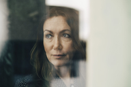 Close-up of mature businesswoman seen through window while looking away - MASF08346
