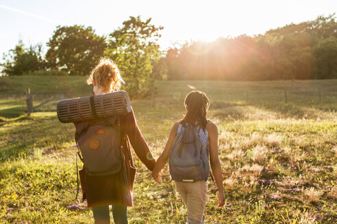 Rear view of girl and woman with backpacks holding hands while hiking on grass at public park during sunset - MASF08439