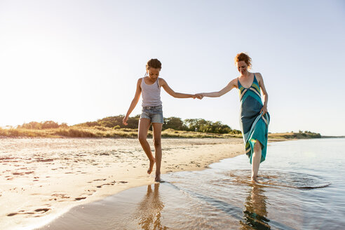 Full length of mother and daughter holding hands while walking on shore at beach against clear sky - MASF08442